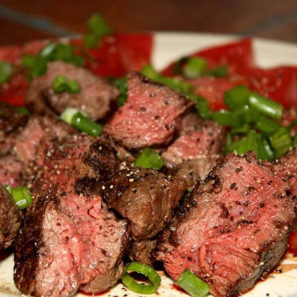 Smoked Beef Tenderloin Roast, Cut Into Smaller Pieces, Served On Dish With Fresh Vegetables.