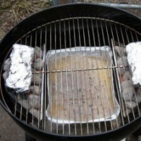 Foil Packet Of Smokerwood On a Weber Charcoal Grill, Releasing Smoke Onto a Grilling Turkey Section.