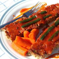 Meatloaf On Plate With a Fork, Topped With Poblano Pepper Sauce and Pepper Slices