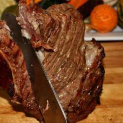 Separating The Meat From a Smoked Beef Rib Roast, Using A Sharp Knife And Two Hands