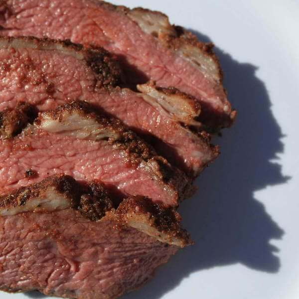 A Traditional Santa Maria Tri Tip, Smoked With Oak, Slices On a White Platter