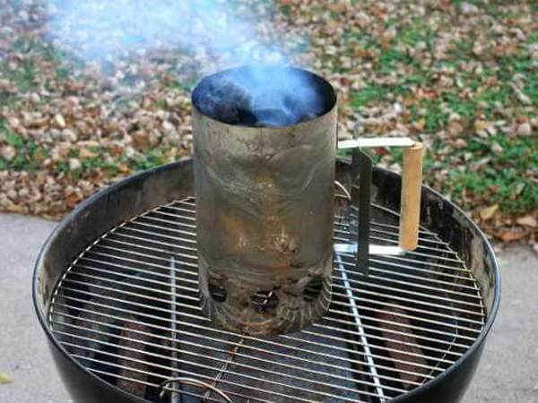 A Charcoal Chimney Resting On a Weber Kettle Grill Grate, Charcoal Briquettes Just Ignited