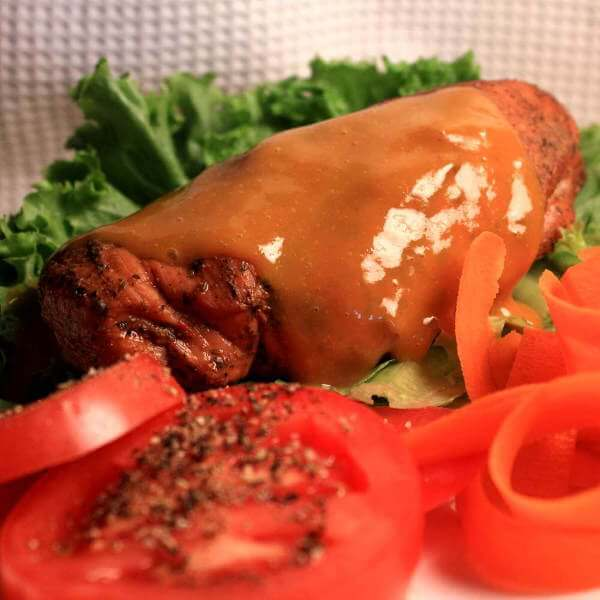 A Closeup Photo Of a Grill Smoked Rosemary Chicken Breast, Served On a Plate With Lettuce, Tomato and Carrots.
