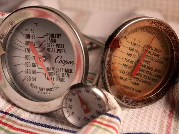Three Analog Dial Smoker and Meat Thermometers Resting On a Patterned Dish Towel