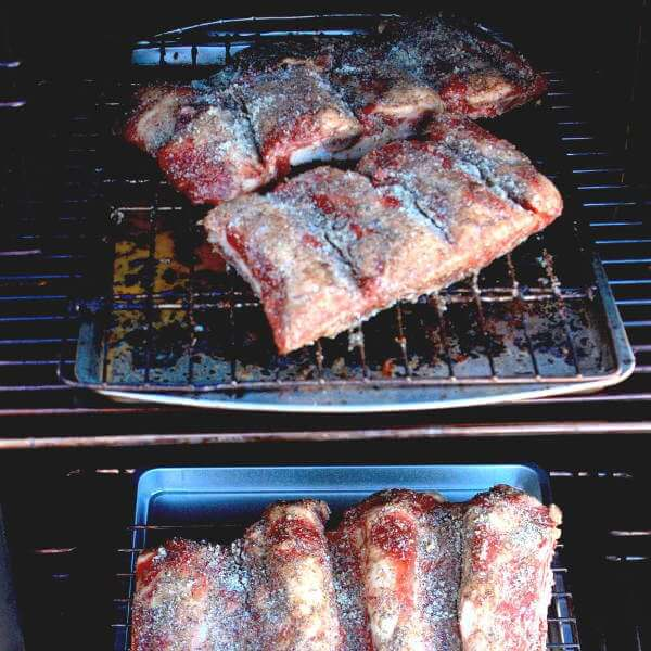Four Half-Slabs Of Beef Ribs, Seasoned With Dry Rub, In a Char-Broil Propane Smoker