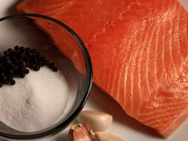 Raw Salmon Fillet On Plate Alongside Garlic Cloves, Whole Peppercorns and Salt