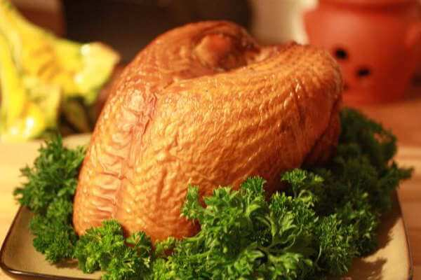 Beautifully Smoked Turkey Breast Resting In a Bed Of Leafy Green Lettuce