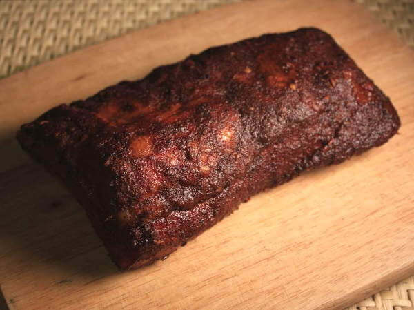 Half-Slab Of Smoked Baby Back Ribs On Cutting Board