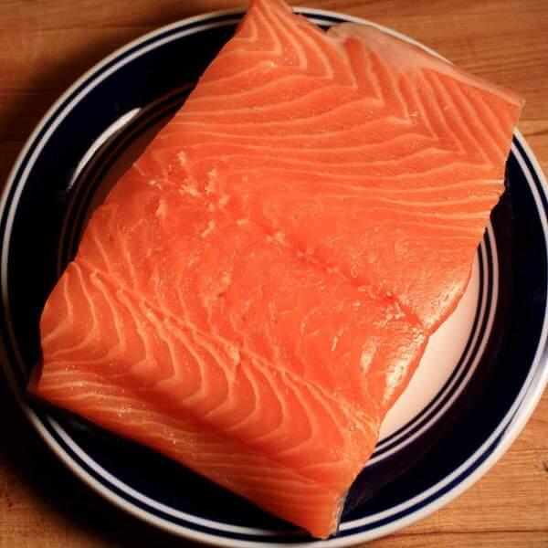 Raw Atlantic Salmon Fillet On Blue-Rimmed Dish