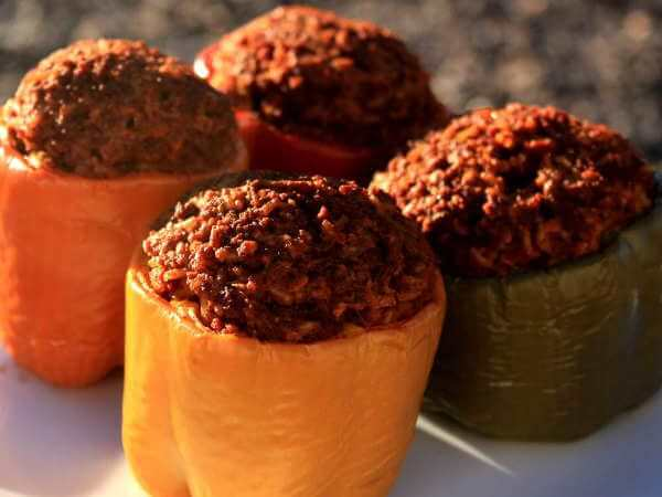 Four Sweet Bell Peppers, Filled With Ground Beef Mixture Then Smoked, On a White Platter