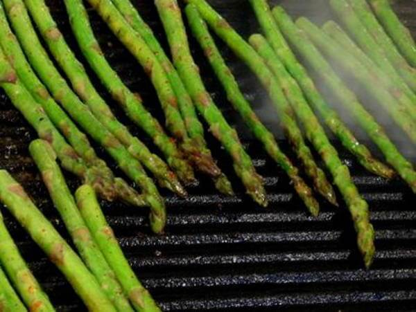 Grilling Fresh Asparagus Spears On a Cast Iron Grill Grate