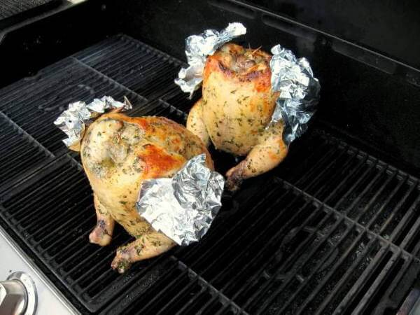 Pair of Whole Chickens Being Grill-Smoked Using The Beer Can Chicken Method