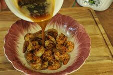 Pouring Seasoned, Brown Butter Over Ancho Shrimp In Colorful Bowl
