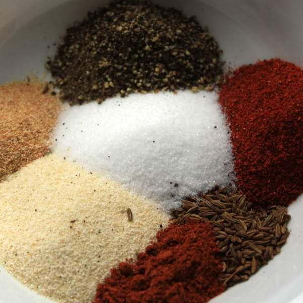 Dry Rub For Chicken, Ingredients In Bowl Before Mixing Include Salt, Onion Powder, Black Pepper and Caraway Seeds