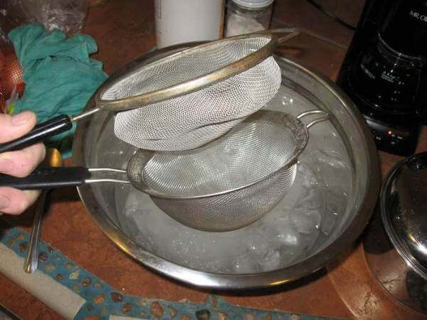 Preparing to Strain The Simmered Brine Mixture With Two Strainers - One Medium Mesh, One Fine Mesh