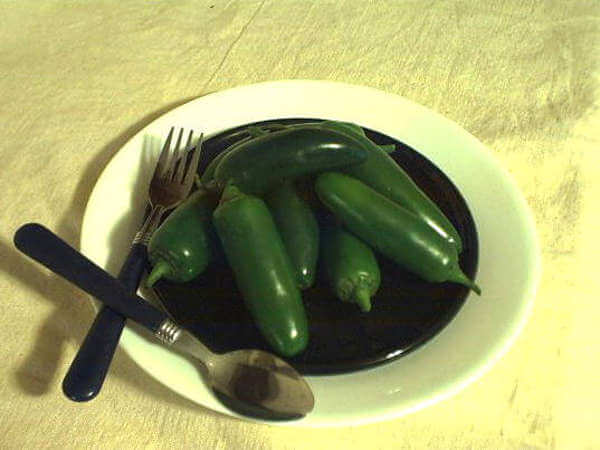 Fresh Jalapeno Peppers On Black Plate With Silverware