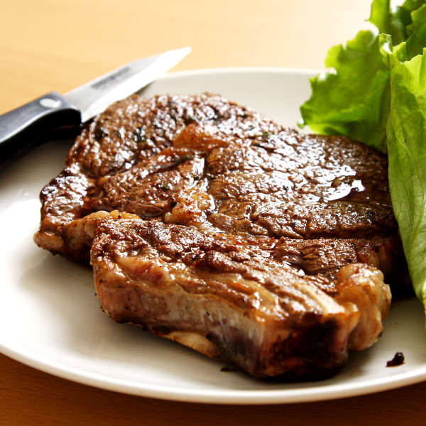 Grilled and Marinated Rib Eye Steak On Platter With Knife and Lettuce Leaves