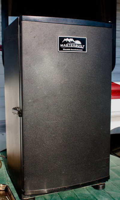 my masterbuilt electric smoker in front of my rv on a green patio table
