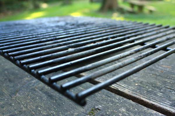 A Dirty Porcelain Grill Grate, On Wooden Picnic Table