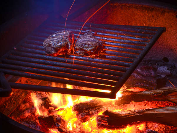 Two Rib Eye Steaks Cooking Over a Wood Fire