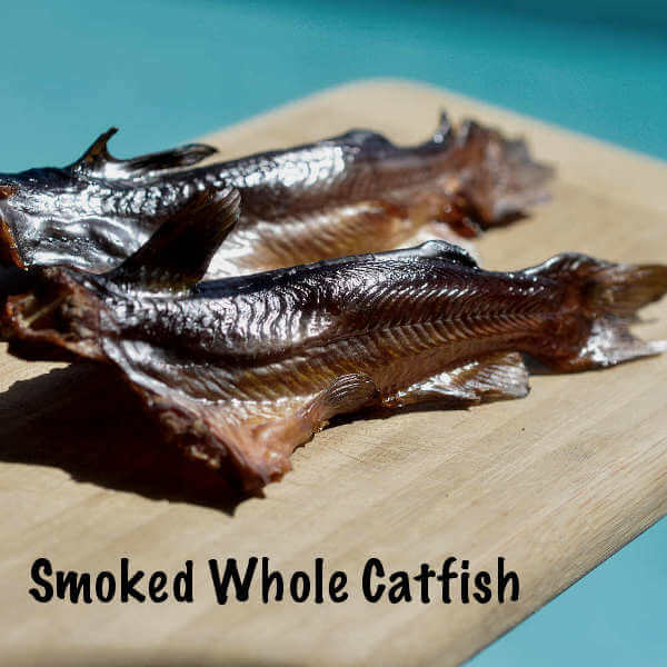 Two Whole Smoked Catfish On a Wooden Cutting Board