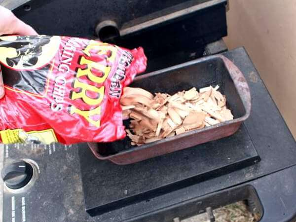 Cherry Wood Chips Being Poured Into Wood Chip Pan Used In Gas Grill