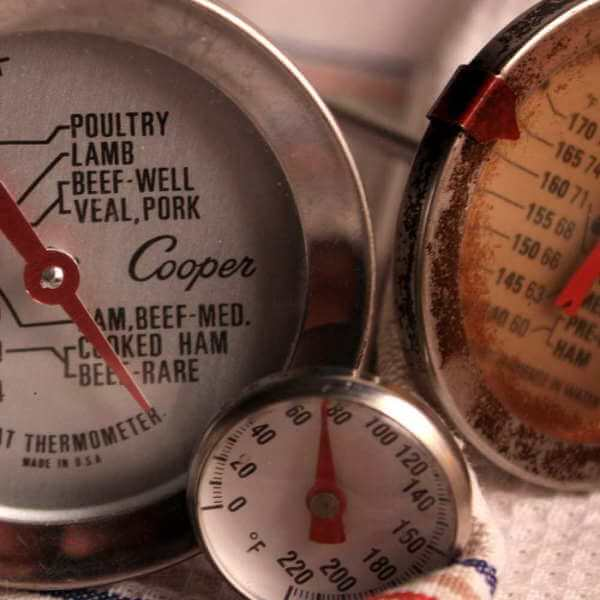 A Group of Analog Meat Thermometers, Resting On a Multi-Color Dish Cloth