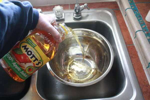 Apple Juice Being Poured Into Bowl for Apple and Spice Turkey Brine Recipe