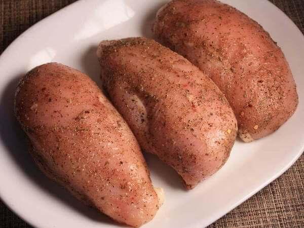 Three Raw, Seasoned, Boneless Skinless Chicken Breasts on White Platter