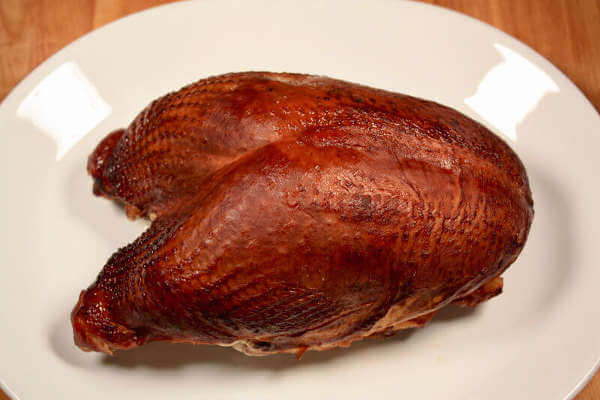 This Nicely Browned Smoked Turkey Breast, On a White Serving Platter, Is Ready To Slice and Serve!