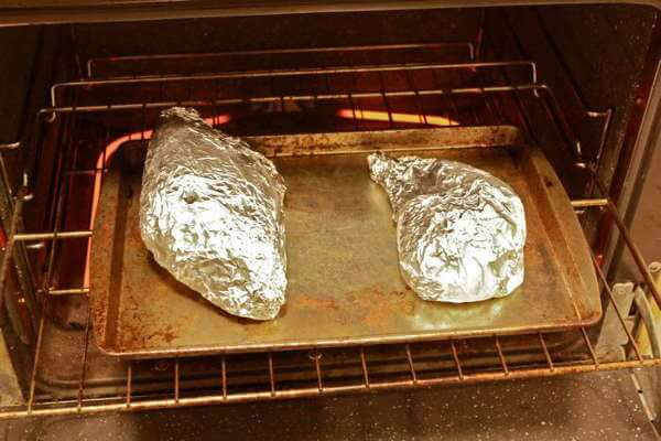 Foil Wrapped Packages of Previously Smoked Turkey Going Into The Oven For Reheating